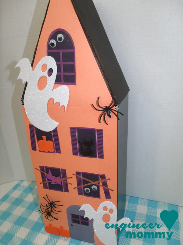Decorating the haunted house with ghosts, pumpkins, black cats and spiders