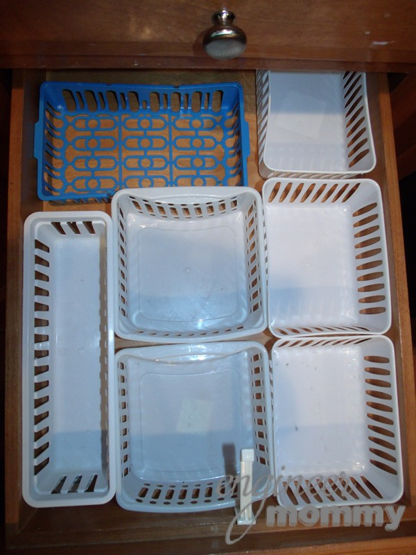 Placing plastic organization baskets in the drawer